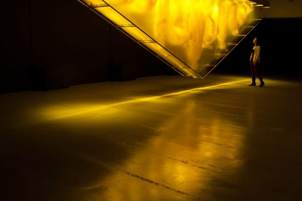GOLD. David Spriggs. 2017. 1097 x 274 x 76 cm. / 432 x 108 x 30 inches. Yellow acrylic paint on layered sheets of transparent film, triangular gold colour structure, lighting units  Gold is the latest in David Spriggs' chromatic artwork series of Stratachromes that examine contemporary symbolic meanings of color. Spriggs' monumental installation presents eleven inverted yellow-golden human figures painted on layers of transparent sheets that are hung within an inverted pyramid structure. Initially reminiscent of the pediment of the New York Stock Exchange, Gold, in the spirit of pittura infamante (defaming portrait) turns the glory of capitalism on its apex, revealing its current precarious state. It speaks to the widening inequity within the Global Wealth Pyramid and the concentration of excessive wealth and corresponding power into the hands of a select few.  It is fitting that this provocative art work is on display in the central business district in downtown Pittsburgh, also known as the Golden Triangle. This historic location dates back to the gilded age. It is to that age the nation's current political leadership seek's to return, in their quest to remake the current America into some idolized great state. But is that even possible or is such a return an illusion? And if not an illusion, will the result be to repeat that period's excesses and failures?  The viewer may be unsettled by the mirage-like-forms and suggestively paganic imagery. Is this intensely-saturated golden color representative of fools or of wealth? Yet we note that the figures of the artwork are not engaged in various forms of industry, in service to a central Goddess of Commerce, but rather are subservient, aloof or apart. Such is the relationship of many with today's economy.